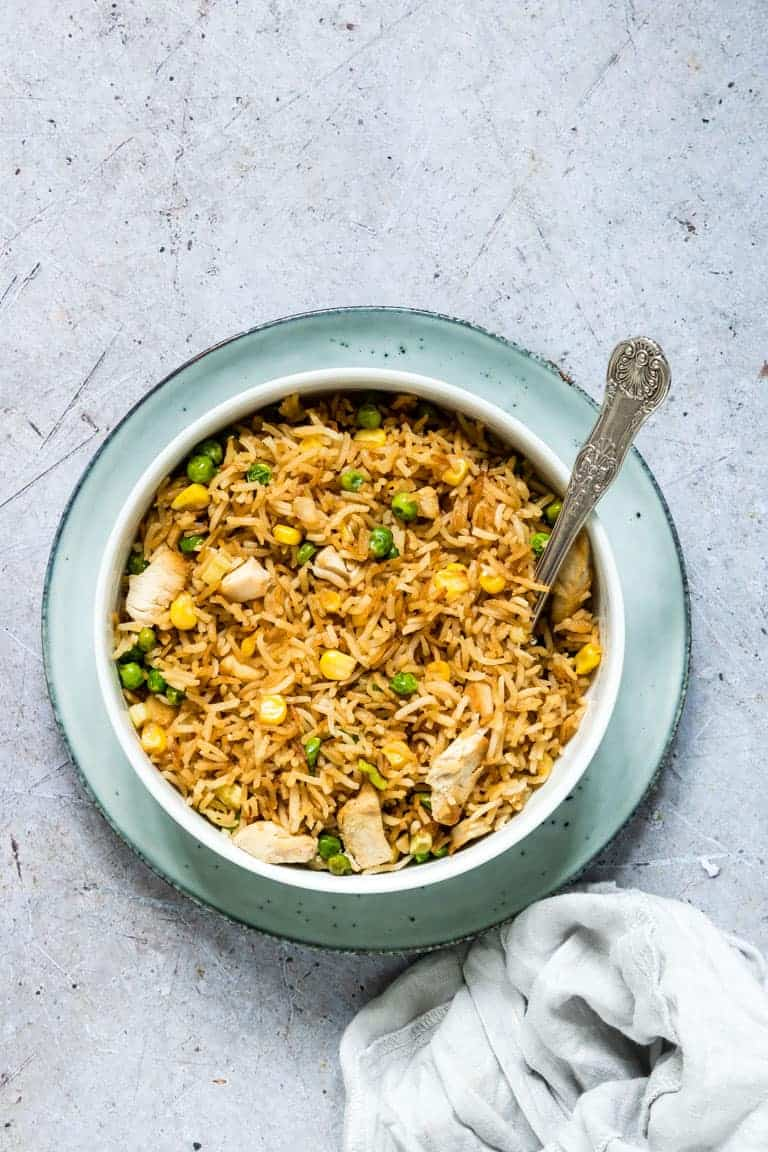 a bowl of air fryer fried rice served with a silver spoon and cloth napkin