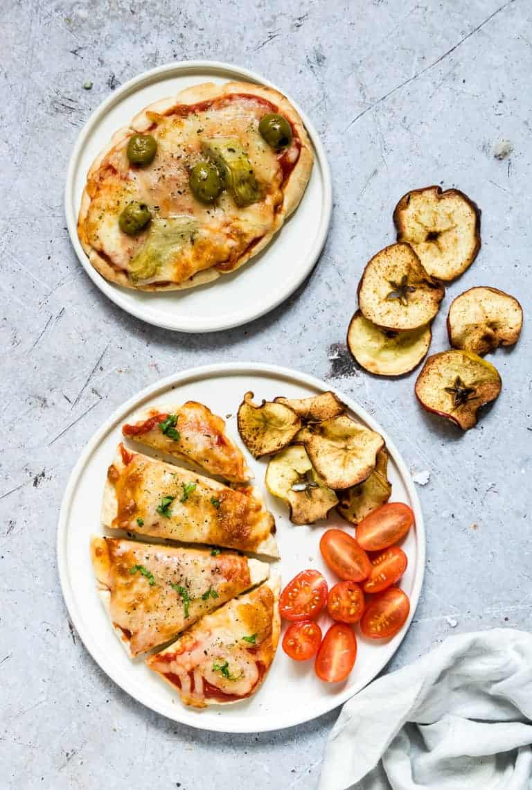a whole air fryer pita bread pizza topped with olives and artichokes placed next to a sliced air fryer pizza served with air fryer apple chips and baby tomatoes