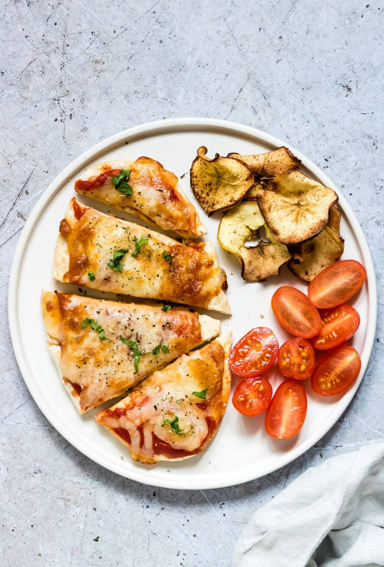 Air Fryer Pita Bread Pizza served on a white plate with a handful of air fryer apple chips and sliced baby tomatoes