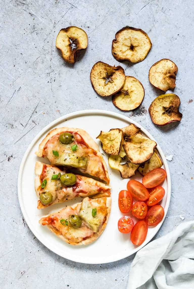Air Fryer Pita Bread Pizza topped with olives and artichokes, cut into pieces and served with air apple chips and sliced cherry tomatoes