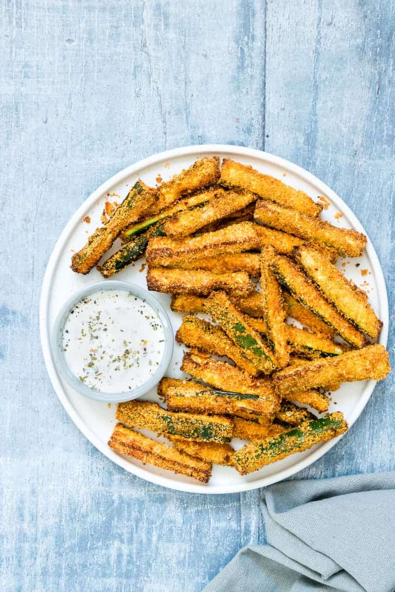 a plate of air fryer zucchini fries with a small glass bowl filled with creamy yogurt herbed dip