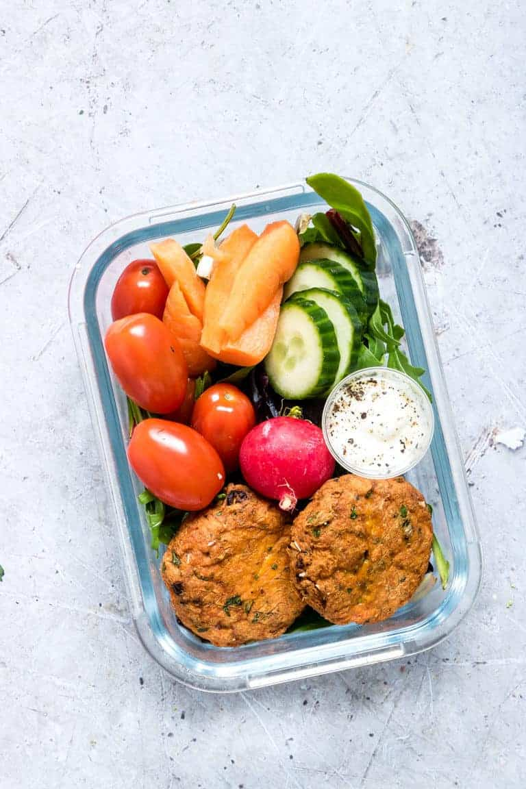 meal prep lunchbox containing two baked salmon patties, baby carrots, sliced cucumber, cherry tomatoes, and a cup of dipping sauce