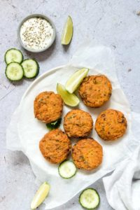Baked salmon patties served on a white plate with lime wedges, sliced cucumber and homemade dipping sauce