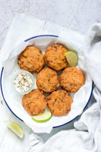 air fryer salmon patties served in a white bowl with lime wedges and dipping sauce