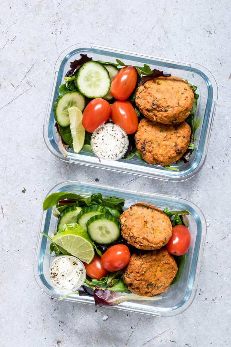 two glass meal prep containers filled with air fryer salmon patties, cut up fresh vegetables, and a cup of homemade dipping sauce