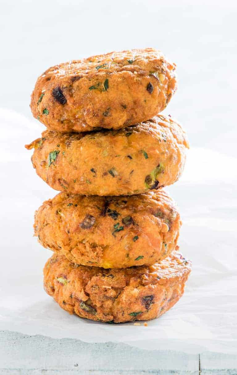 close up view of four air fryer salmon patties stacked in top of each other