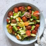 cucumber tomato salad served in a blue bowl