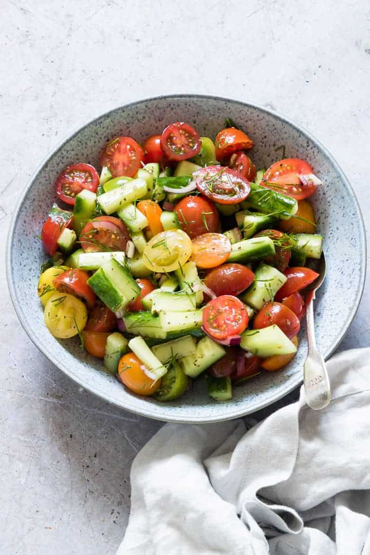 blue bowl filled with cucumber tomato salad and served with a spoon and white cloth napkin