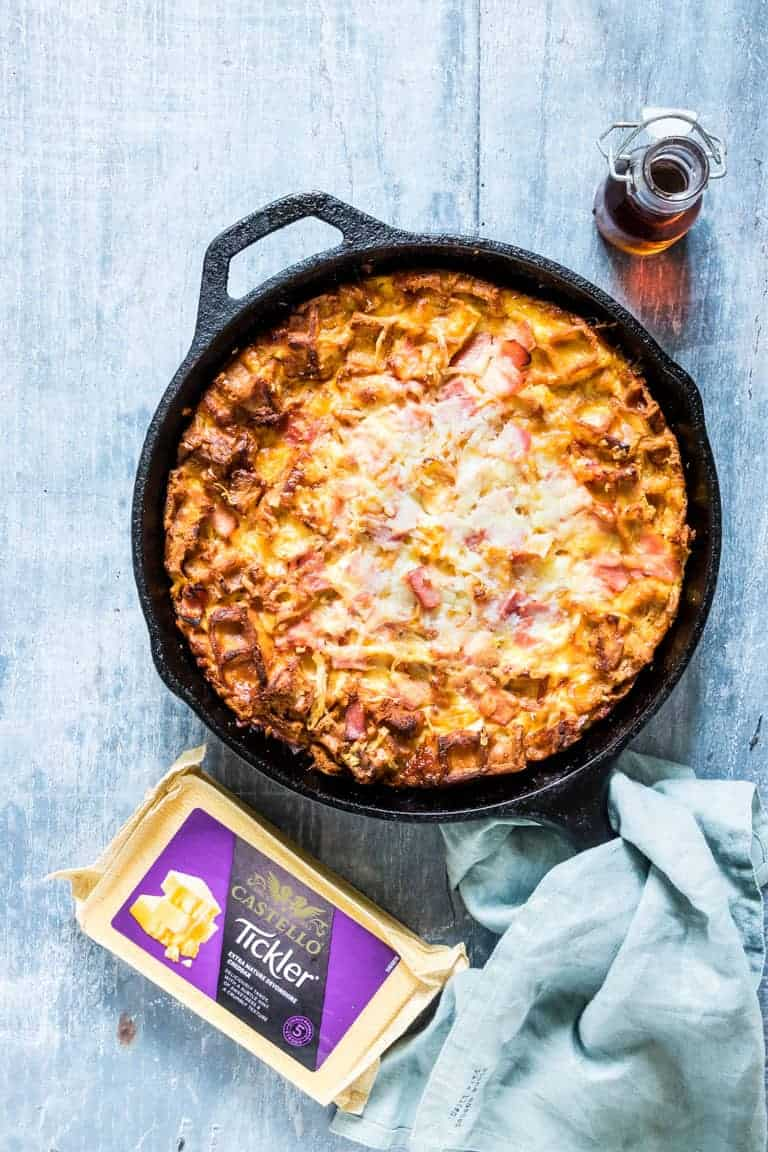 baked cheesy waffle and ham breakfast casserole in a skillet and ready to be served