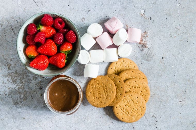 marshmallows, nutella, strawberries and biscuits set out on a countertop