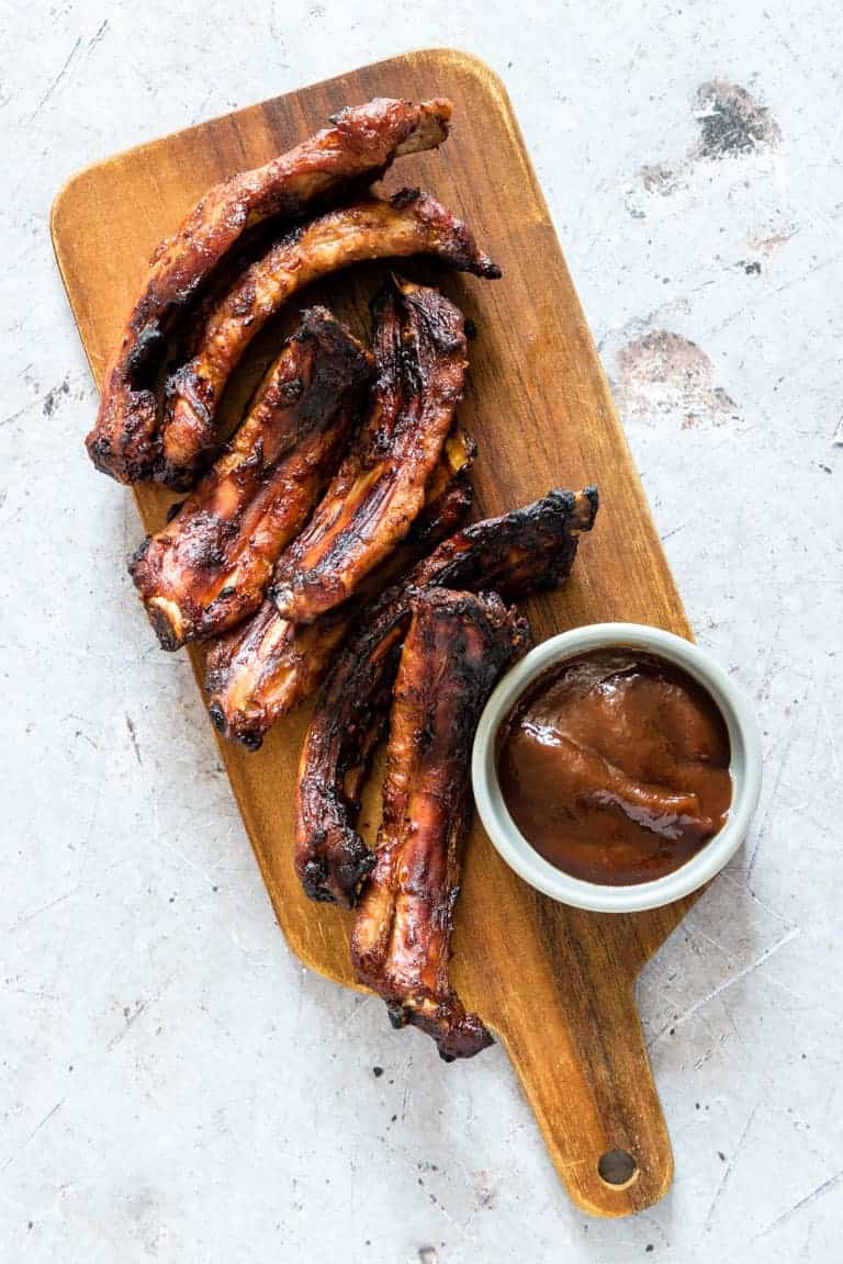 air fryer ribs on a wooden cutting board with a white ramekin filled with bbq sauce
