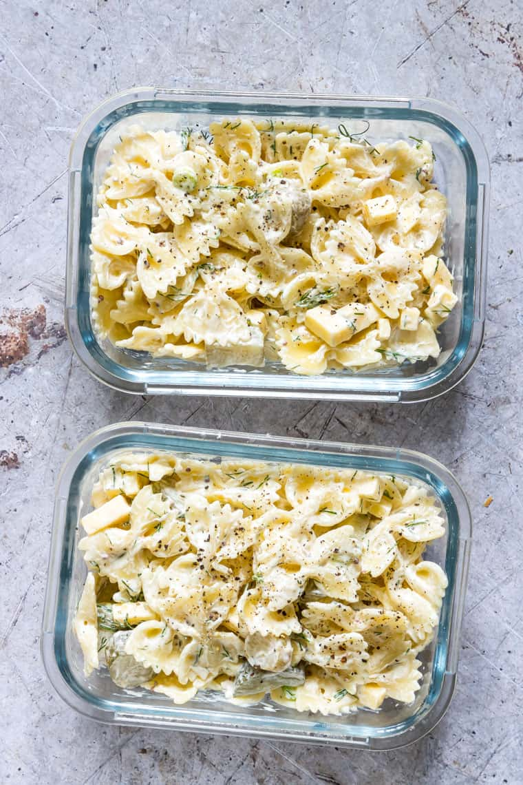 two glass meal prep containers filled with dill pickle pasta salad