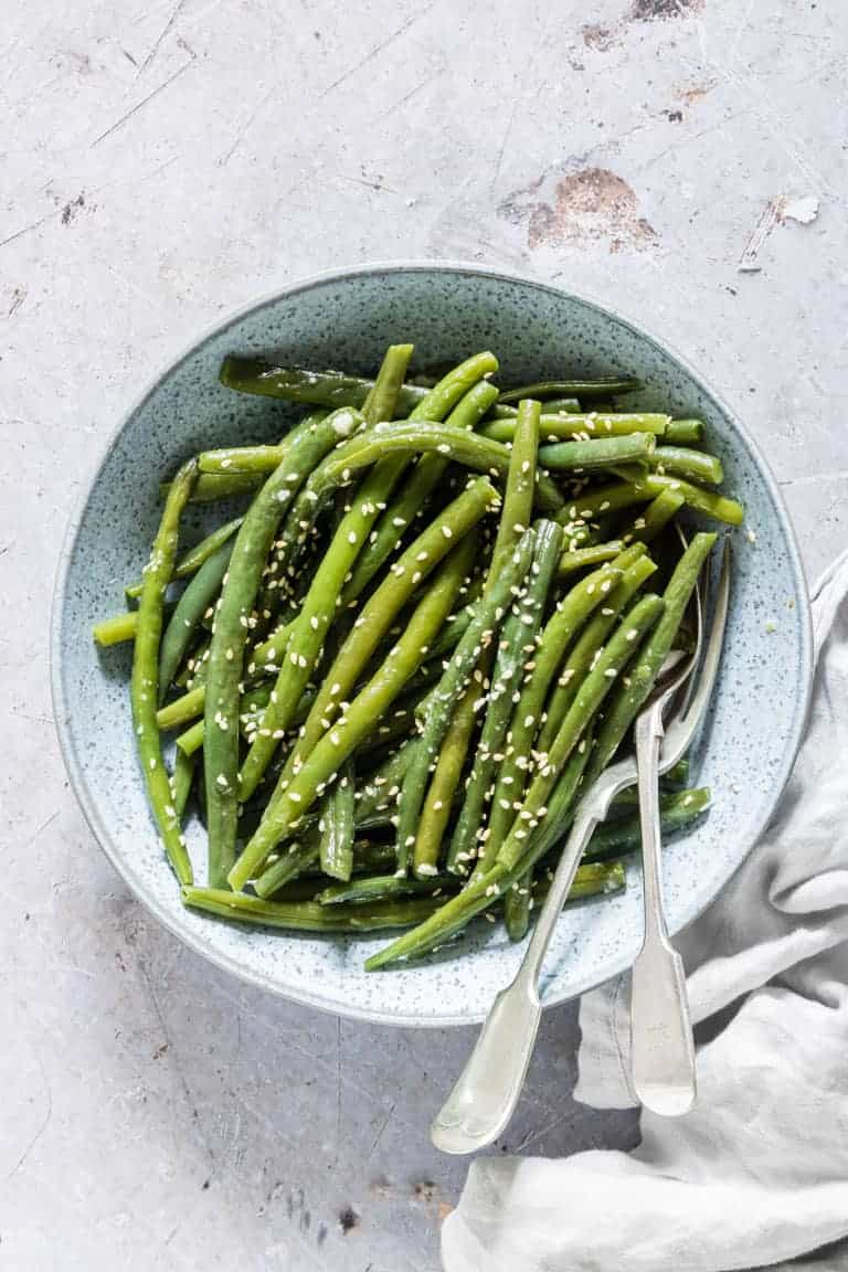 garlic butter sesame instant pot green beans served in a blue bowl with a fork and spoon