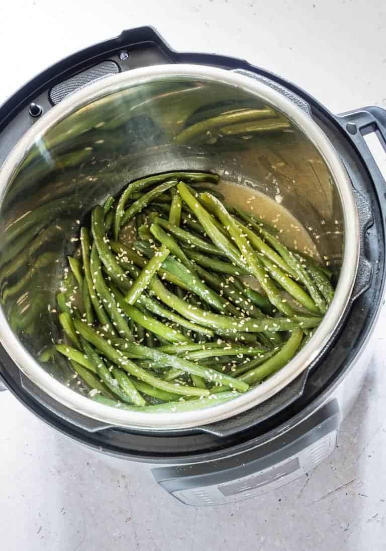 cooked garlic butter sesame instant pot green beans inside the instant pot and ready to be served