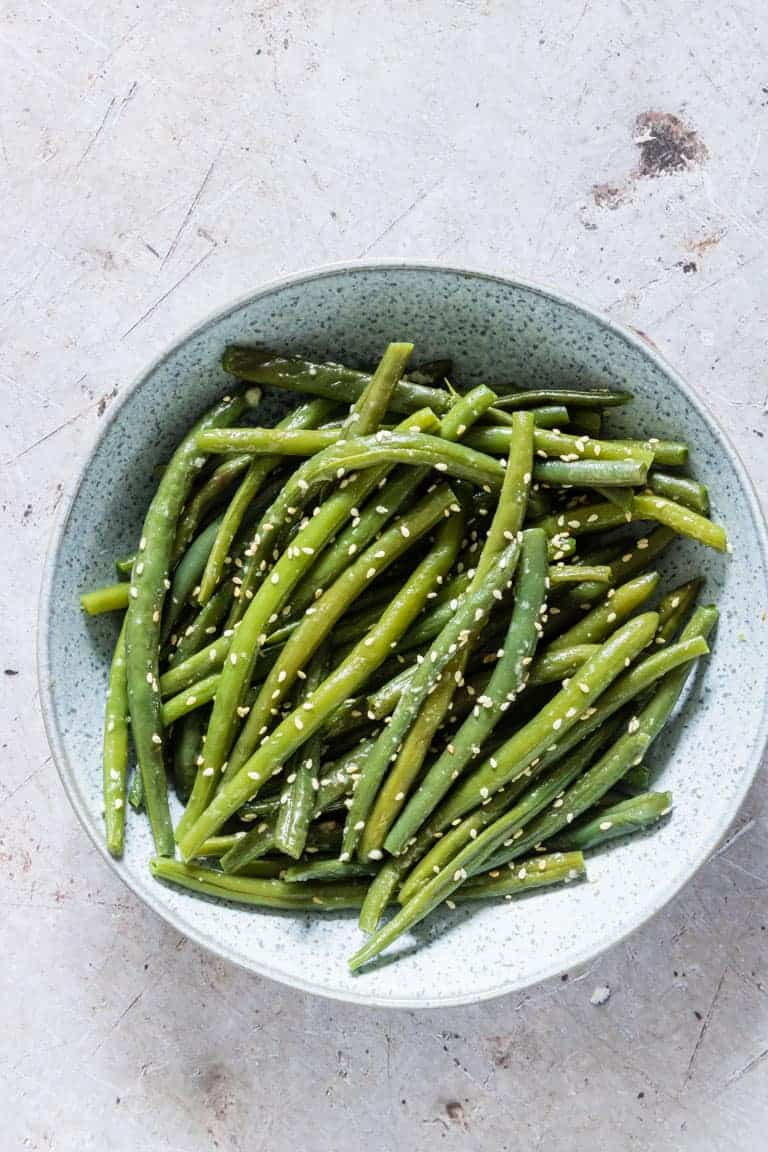 close up view of garlic butter sesame instant pot green beans in a bowl and ready to servr