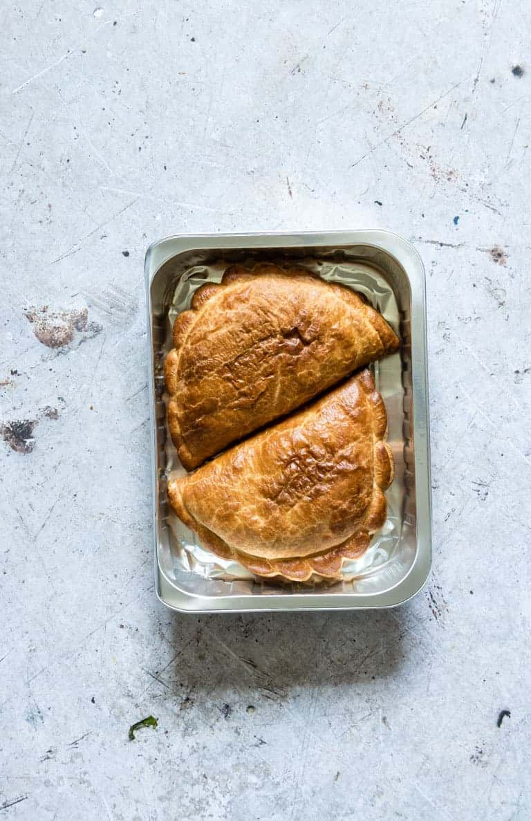 two pasties inside the aluminum bake in tray
