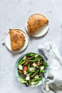 bowl filled with roasted asparagus salad served with two cornish pasties