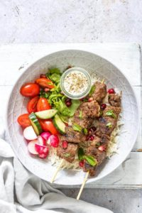 plate filled with 2 lamb shawarma skewers, salad and tahini sauce