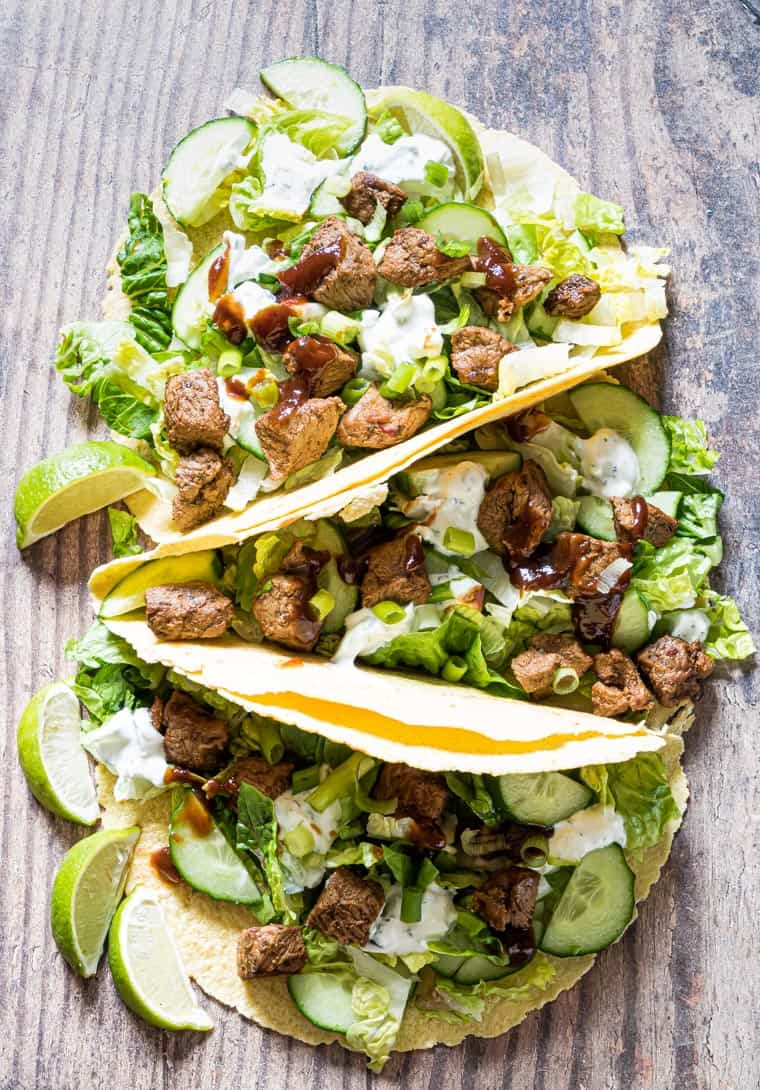 three grilled lamb tacos on a wooden serving board
