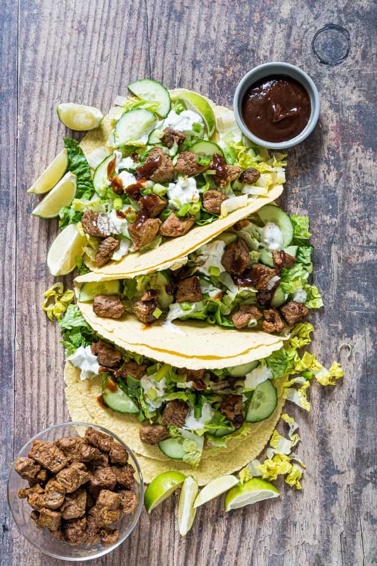 grilled lamb tacos on a wooden serving board with a cup of chipotle sauce and small bowl of grilled lamb