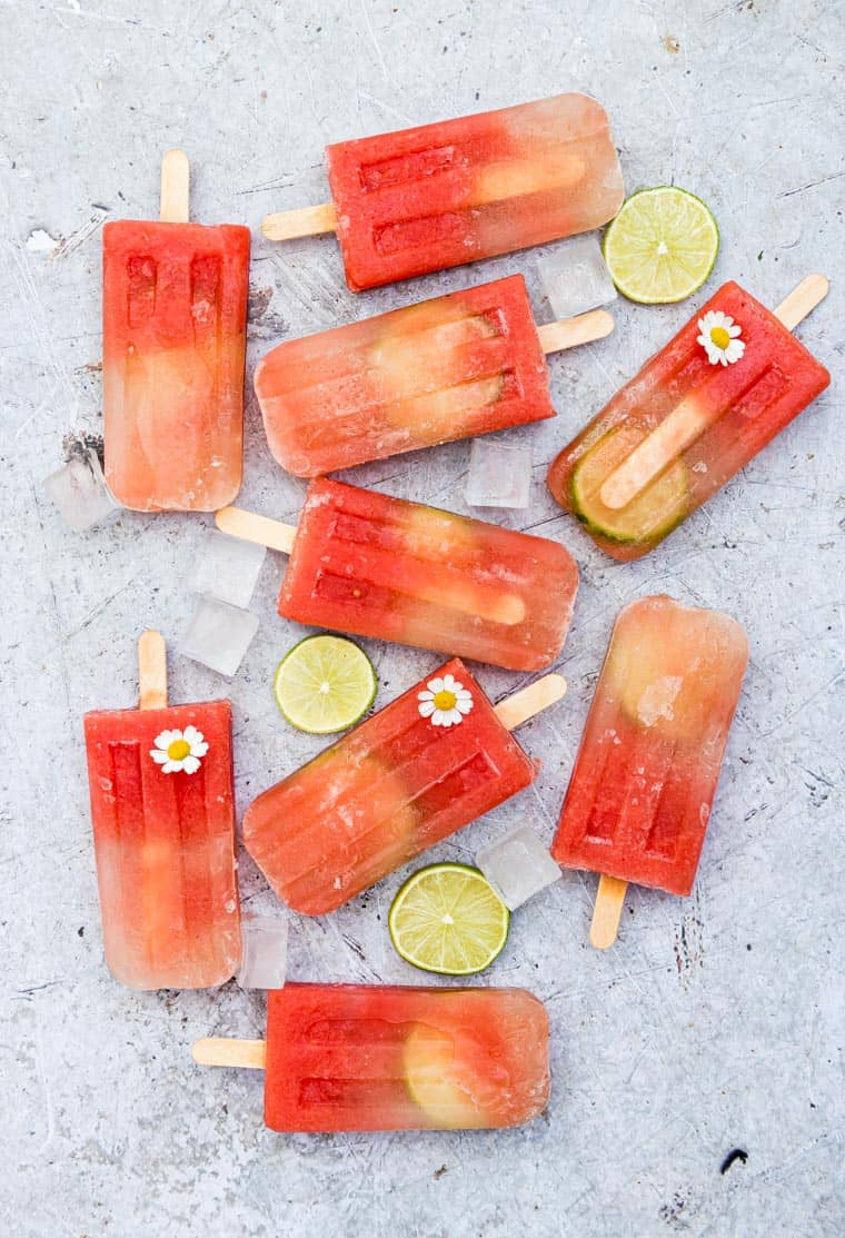 salted watermelon popsicles on a table with lime slices and flowers