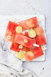 watermelon margarita popsicles on a plate with flowers and lime