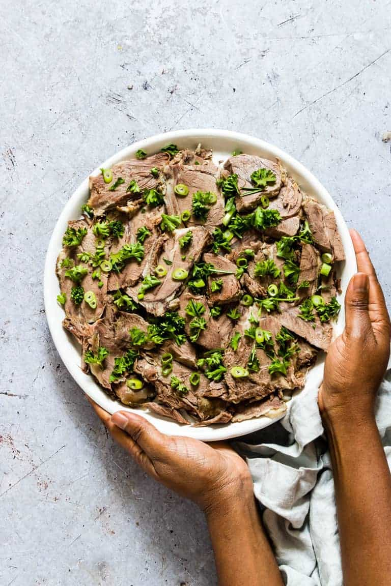 A platter of Instant Pot Lamb Shoulder sliced and garnished with parsley and green onions