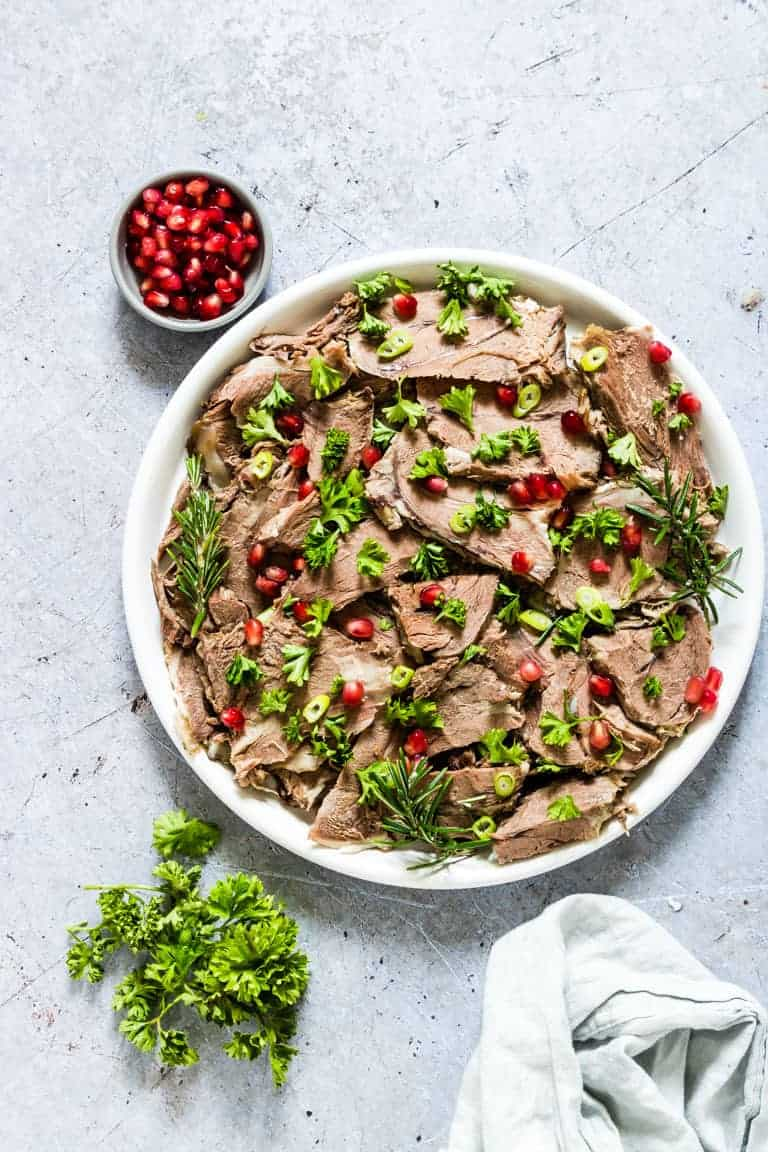 A platter of sliced Instant Pot Lamb Shoulder garnished with fresh herbs and pomegranate seeds