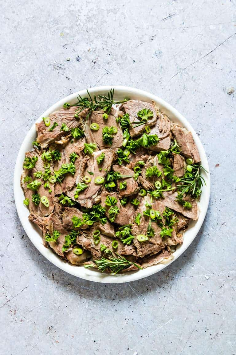 A platter of sliced Instant Pot Lamb Shoulder garnished with fresh herbs and sliced green onions ready to be served