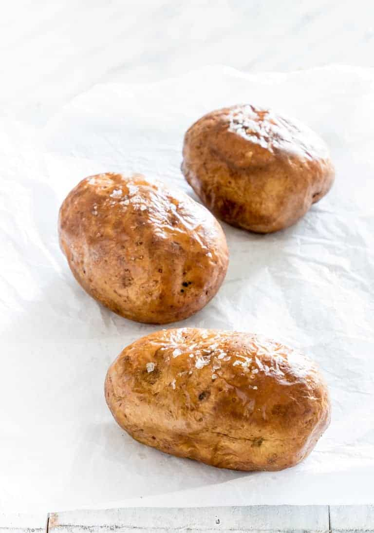 three potatoes on a countertop seasoned and ready to be put in the air fryer to make air fryer baked potatoes