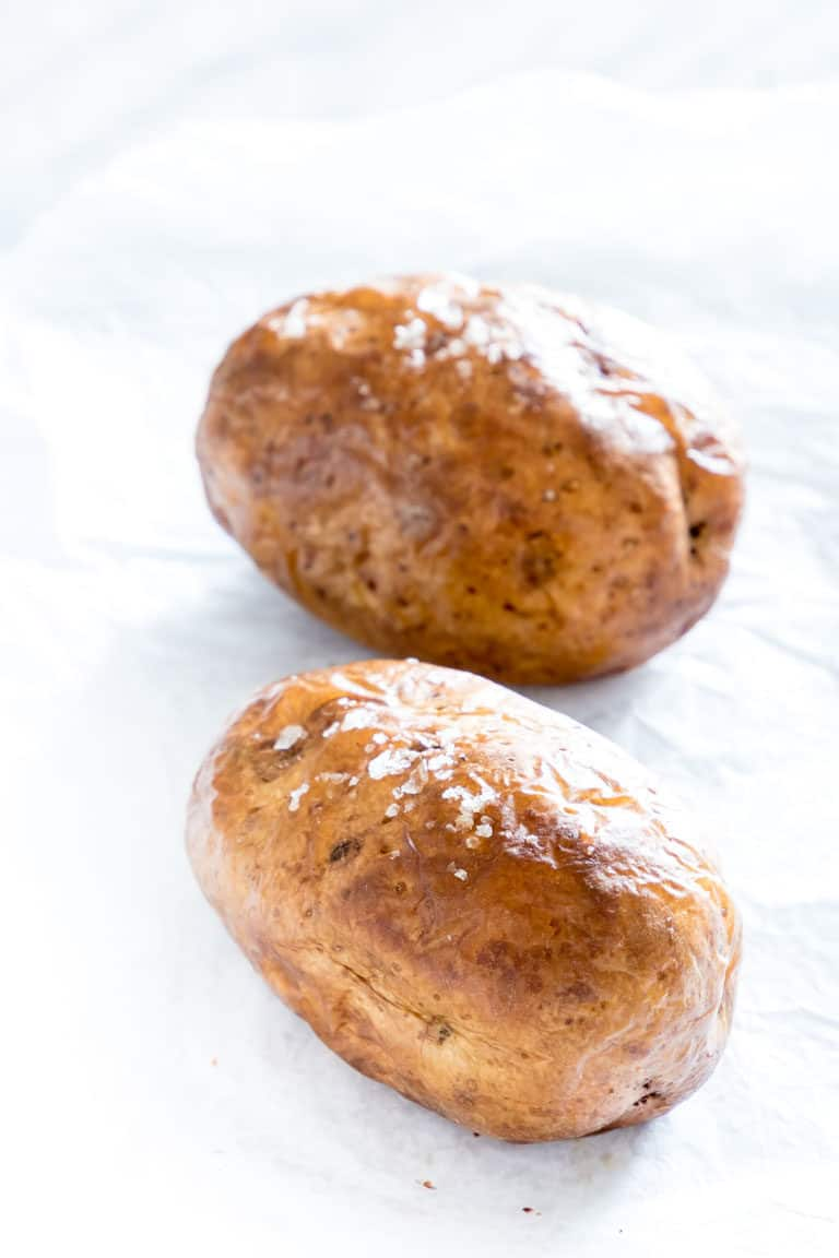 two air fryer baked potatoes on a counter and ready to serve